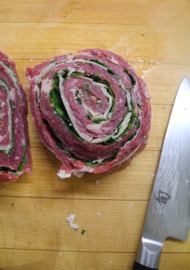 A pinwheel steak stuffed with parsley and Parmesan, ready to be cooked.